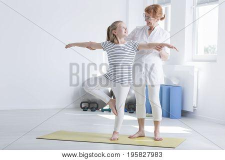 Child Exercising With Female Physiotherapist
