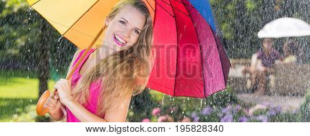 Optimistic woman with colorful umbrella during downpour in the park