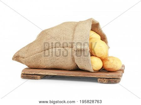 Sack with potatoes on wooden board against white background