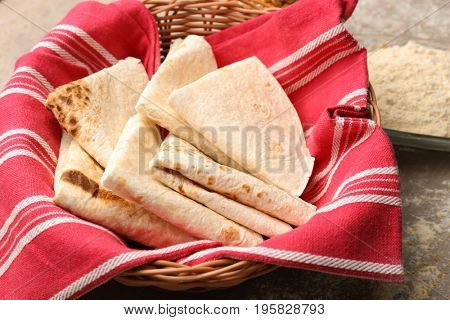 Basket with yummy tortillas on kitchen table