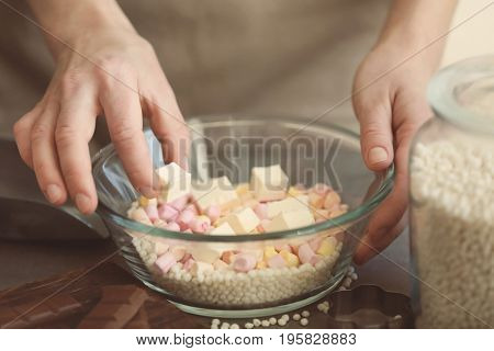 Woman holding bowl with ingredients for rice dessert on table