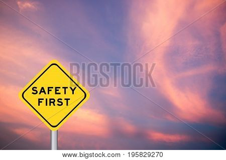 Safety first wording on yellow transportation sign with violet cloud sky background