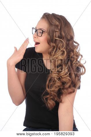 young woman with glasses yawns on white background