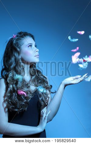 fashion portrait of girl with feathers in blue light