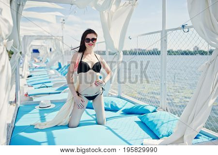 Portrait Of An Amazing Girl In Black Bikini Swimsuit Posing On Her Knees On Lounger By The Lake.