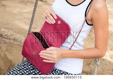 Closeup woman hands with luxury handmade snakeskin handbag, outdoors, fashion look. Asia, Bali, Indonesia