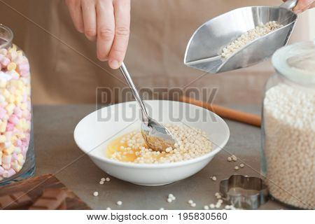 Woman adding crispy rice balls into bowl on table