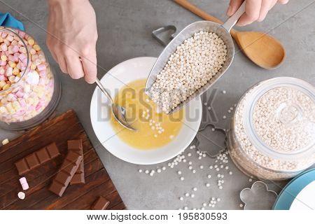Woman adding crispy rice balls into ceramic bowl on table