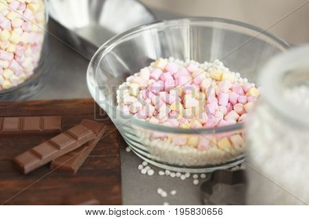 Glass bowl with crispy rice balls, marshmallow and chocolate bars on table