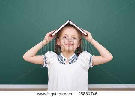 School girl read book, posing at school board, empty space, education concept