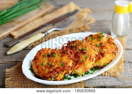 Easy potatoes ham cutlets. Roasted potato cutlets with ham on a white plate and a vintage wooden background. Rustic style. Closeup