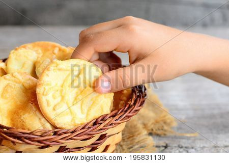 Small child takes a cheese cookie from a basket. Butter cheese cookies in a wicker basket on a vintage wooden background. Closeup