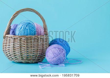 wool yarn balls in basket  on plain aquamarine background