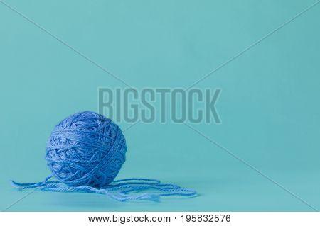 ball of yarn on plain aquamarine background