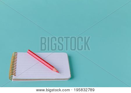 Open Spiral Blank Notebook With Pencil On Aquamarine Desk Background