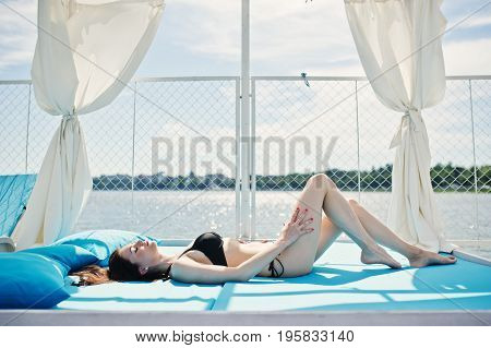 Portrait Of A Beautiful Girl In Black Bikini Swimsuit Laying On The Lounger By The Lakeside.