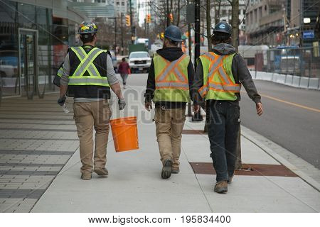 Three males safety jackets walking along street Vancouver Canada