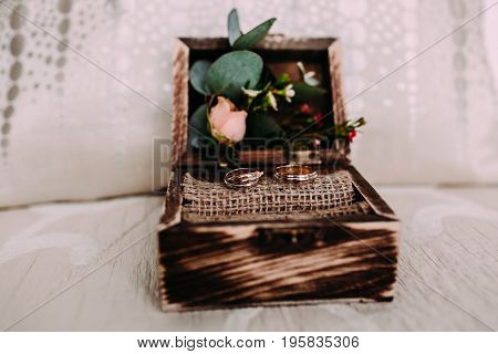 Golden wedding rings in the beautiful rustic box with flowers inside and on the light background. Close-up. Selective focus