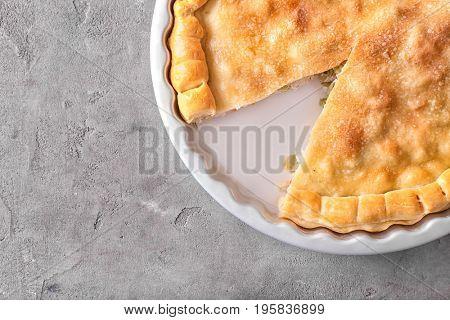Baking dish with turkey pot pie on gray background