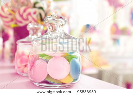 Tasty candies in jar on table