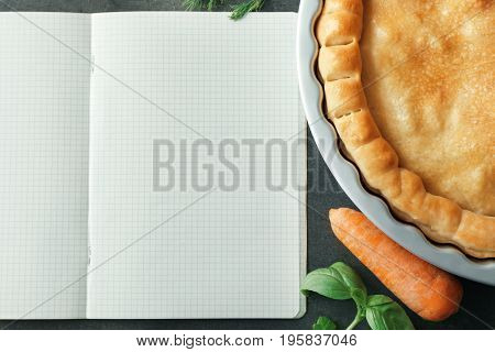 Open notebook and tasty turkey pot pie with ingredients on gray background, closeup