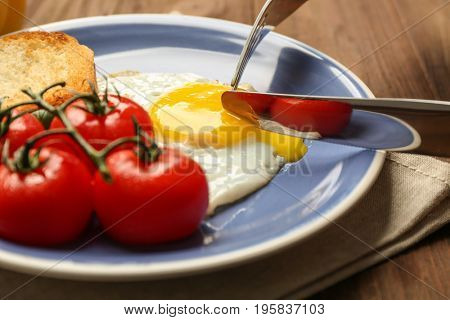 Knife and fork with delicious over easy egg on plate, closeup