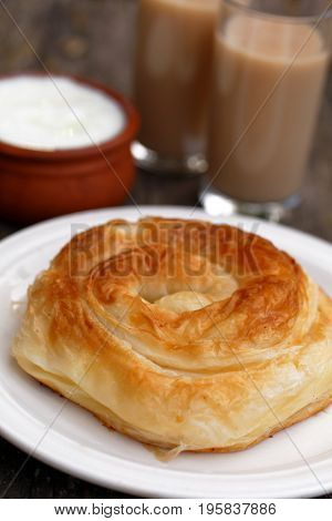 Traditional Bulgarian pastry Banitsa on a rustic table with Greek yogurt and fermented beverage boza