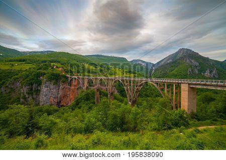 Durdevica arched Tara Bridge over green Tara Canyon at evening time - Montenegro