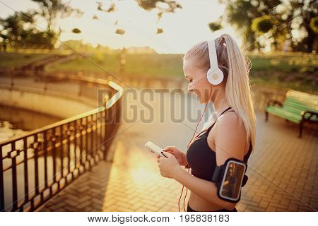 Girl runner stand in the park listening to music on headphones with phone.
