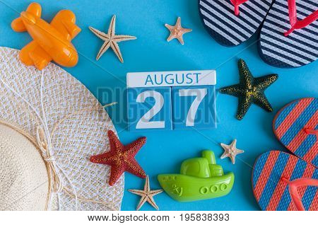 August 27th. Image of August 27 calendar with summer beach accessories and traveler outfit on background. Summer day, Vacation concept.