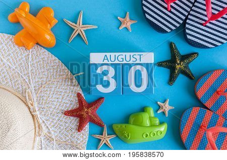August 30th. Image of August 30 calendar with summer beach accessories and traveler outfit on background. Summer day, Vacation concept.