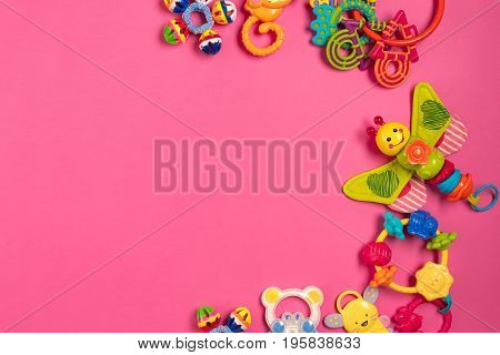 Children's rattle from plastic on a pink background. Top view. Copy space. Flat lay