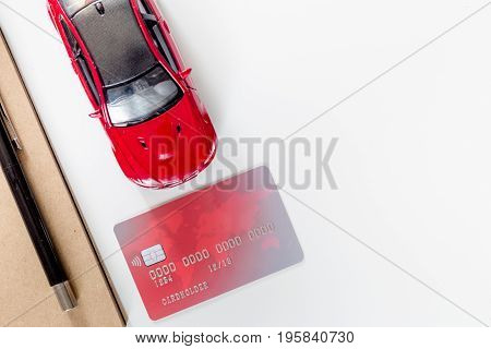 Buying car. Toy cars and bank card on white background top view.