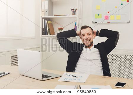 Young relaxed businessman with laptop in office interior. Handsome man, confident and successful employee at work with computer. Lifestyle portrait
