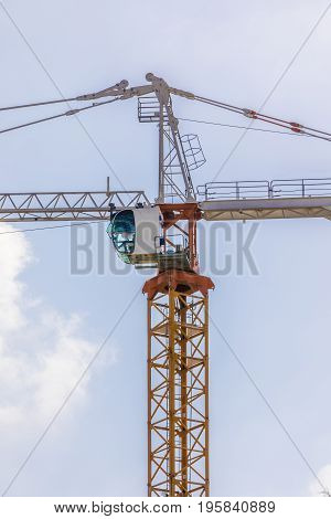 Construction tower crane cabin in the blue sky and clouds vertical