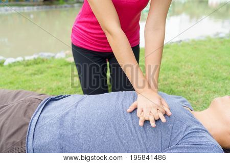 Woman giving cardiopulmonary resuscitation (CPR) to a man at public park poster