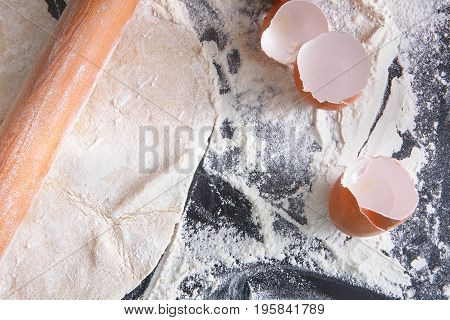 Baking pizza concept. Hand-rolled dough, eggshell and pouring flour on black kitchen table background with copy space.