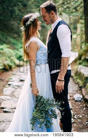 beautiful bride in a blue dress and a wreath of white flowers with the bride are in the wood.