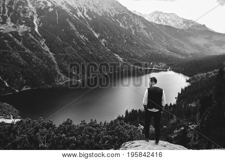 the groom stands on a background of mountains and lakes