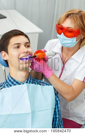 Beautiful woman dentist treating a patient teeth in dental office. Doctor wearing glasses mask white uniform and pink gloves. Dentistry