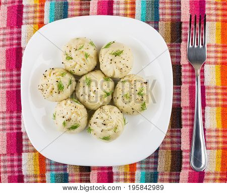 Boiled Khinkali With Dill In Plate And Fork On Napkin