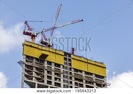 Two tower cranes on top of the building under construction with cables down safety net