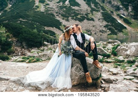 the bride and groom sitting on a large stone overlooking the green mountains