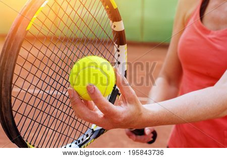Female tennis player with racket ready to serve a tennis ball
