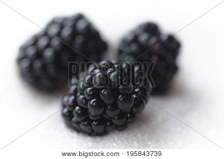 Image of sweet blackberry isolated over white sugar background.
