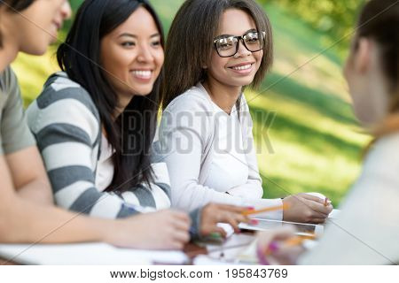 Photo of multiethnic group of happy young students sitting and studying outdoors while talking. Looking aside.