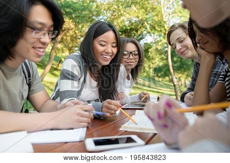 Photo of multiethnic group of smiling young students sitting and studying outdoors while talking. Looking aside.
