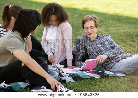 Picture of multiethnic group of young students sitting studying outdoors. Looking aside.