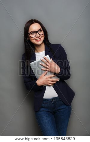 Smart solutions. Beautiful business woman at gray studio background with tablet smiling at camera