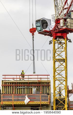 Construction worker wearing yellow hard hat and safety vest standing on building constructing site with crane on side vertical